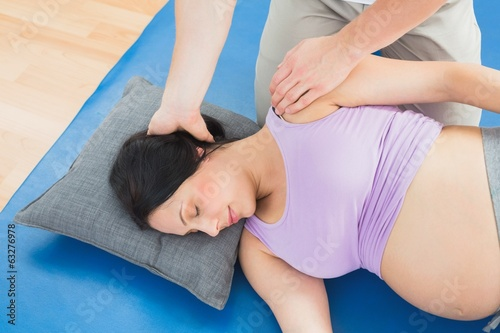 Masseur moving pregnant womans neck and shoulder