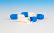 Colorful medical capsules on blue background.