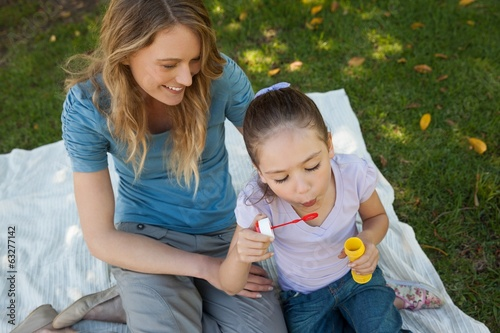 Mother with her daughter blowing soap bubbles at park