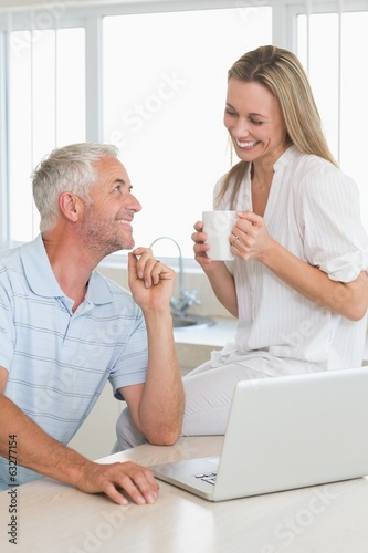 Cheerful couple using laptop together smiling at each other