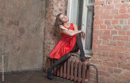 Beautiful slim woman sitting on the windowsill