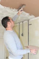 A plasterer plastering a ceiling