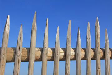 spitziger Holzzaun, blauer Himmel