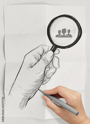 hand holding magnifier glass looking for employee on crumpled pa
