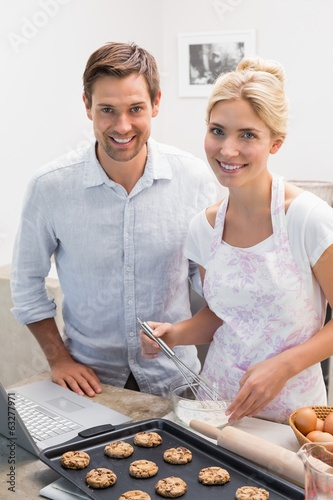 Portrait of young couple preparing cookies in kitchen