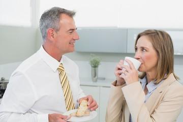 Happy business couple having breakfast in kitchen