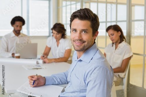 Smiling businessman with colleagues in meeting in at office