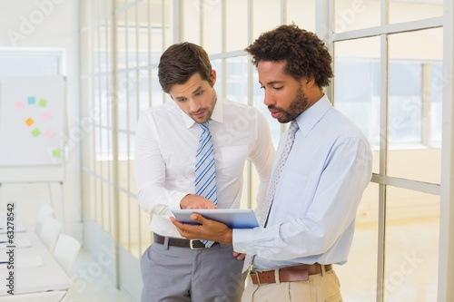 Businessmen looking at digital tablet in office