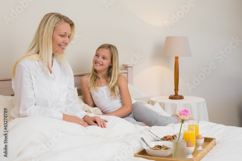 Mother and daughter with breakfast tray in bed