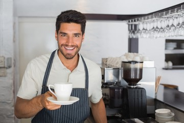 Smiling male barista holding cup of coffee at café