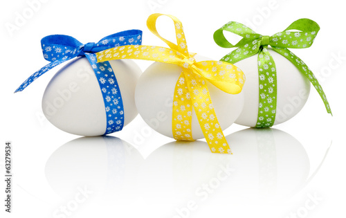 Three Easter eggs with festive bow isolated on white background