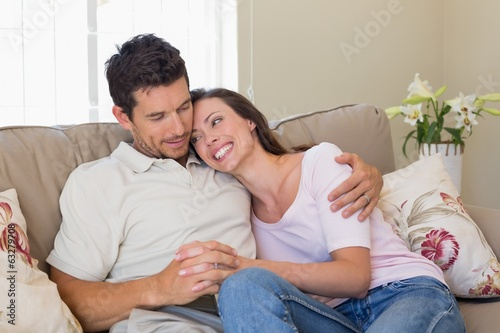 Loving couple sitting on couch at home