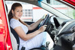 Attractive woman holding car wheel through the opened door