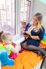 Young girl with mother read books and sitting on the windowsill