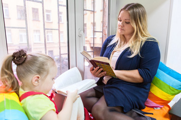Little girl with mother read books on the windowsill