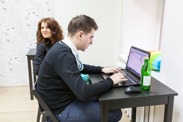 Young man typing with laptop and cheerful girlfriend near