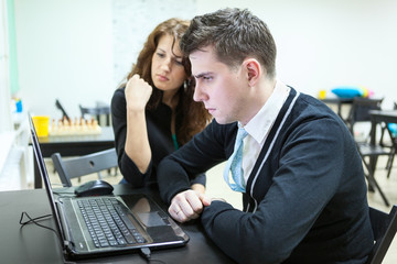 Young couple reading some text on laptop screen