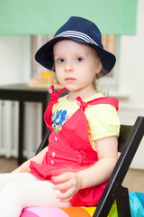 Portrait of little girl in blue hat sitting on chair
