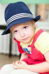 Portrait of little Caucasian girl in blue hat