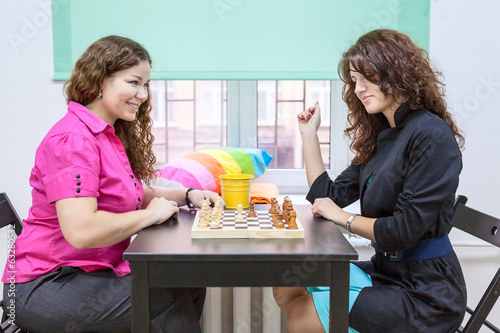 Two young cheerful women playing chess together