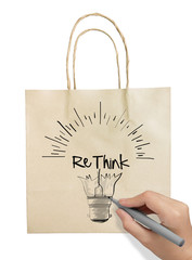Hand drawn light bulb with RETHINK word paper recycle bag on whi