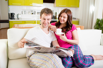 Young married couple in pajamas sitting in the sofa with newspap