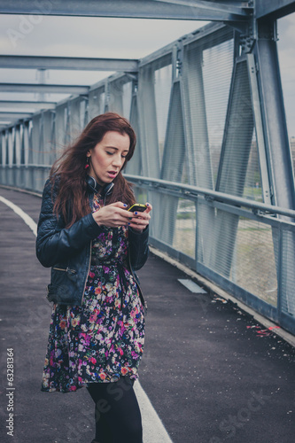 Pretty girl texting on a bridge