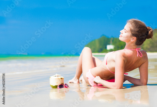 Happy young woman on the beach with coconut cocktail and