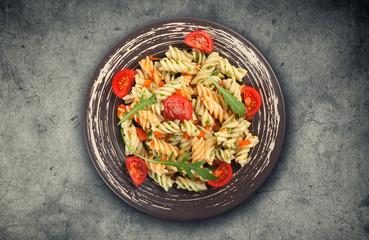 Fusilli pasta with tomato sauce, basil and arugula
