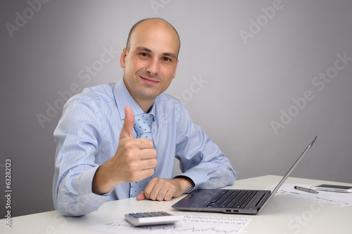 business man working on laptop and making the ok gesture