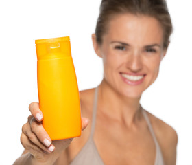 Closeup on happy young woman showing sun screen bottle