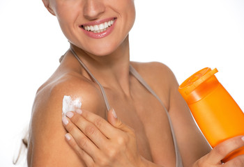 Closeup on happy young woman applying sun screen bottle