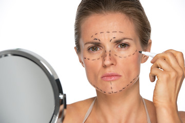 Concerned young woman applying plastic surgery marks