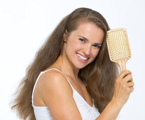 Portrait of happy young woman with hairbrush