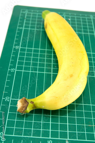 Banana on cutting mat on white background