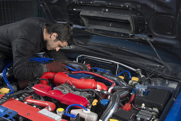 Car repairman examining modified rally car