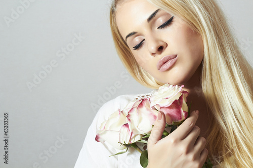 Beautiful Woman with Flowers.girl and roses. Blond