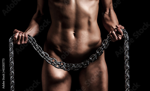 Strong woman with a metal chain, black background