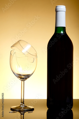 Vine bottle and broken glass on orange background