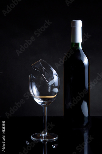 Vine bottle and broken glass on dark background