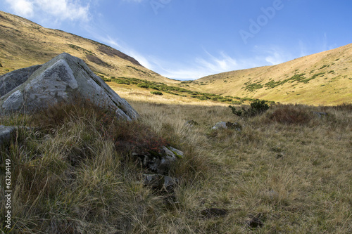 large gray stone in the mountains under the sky