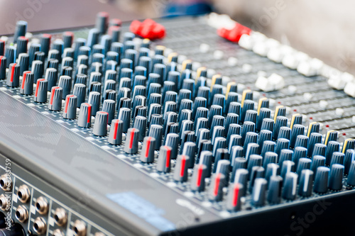 Close-up of sound mixer control panel with many controls