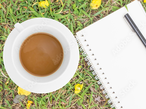 cream notebook with pen and cup of coffee