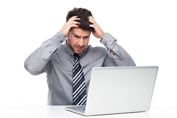 Stressed man looking at laptop