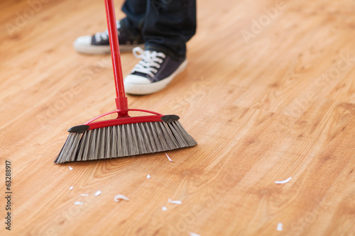 close up of male brooming wooden floor