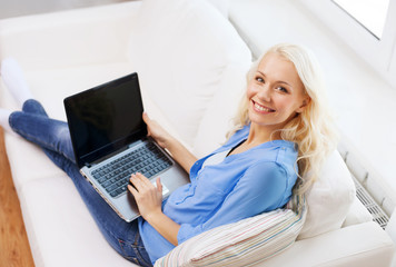 smiling woman with laptop computer at home