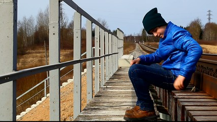 Teenage throw stones from the railway bridge