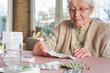 Leinwanddruck Bild - Elderly woman with pills