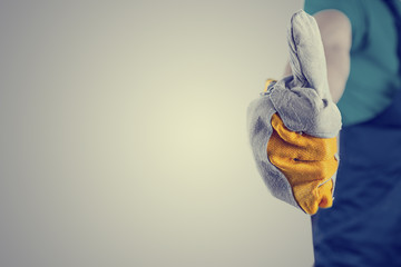 Hand in a protective glove making thumbs up sign