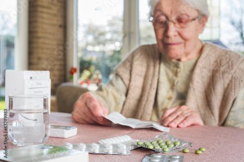 Leinwanddruck Bild Elderly woman with pills